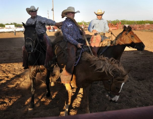 Photo Credit: Ronald W. Erdrich/Reporter-News Cody Aaron (left) reaches out to Cody Heck as he and pickup man Jeff Flowers ride in behind during the ranch bronc riding event at the Wild Horse Prairie Days rodeo Friday in Haskell, June 7, 2013. (Big Country Journal)